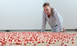 """Searle contemplates the red and white capsules that rain, one every three seconds, from the ceiling. Photograph: Christian Sinibaldi for the Guardian"""